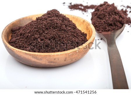 Superfood dried acai berry powder in wooden bowl and wooden spoon over white background
