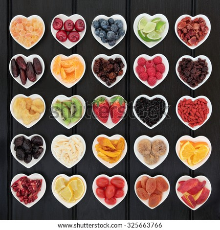 Superfood fruit selection in heart shaped bowls over wooden black background. - stock photo