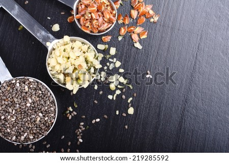 Superfoods. Chia seeds, hemp seeds and broken flax seeds in measuring spoons - stock photo