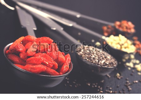 Superfoods. Goji berries, chia seeds, hemp seeds and broken flax seeds in metal measuring spoons, toned - stock photo