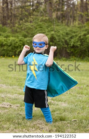 Superhero!  Adorable little boy dressed in a cape and mask playing superhero.   - stock photo
