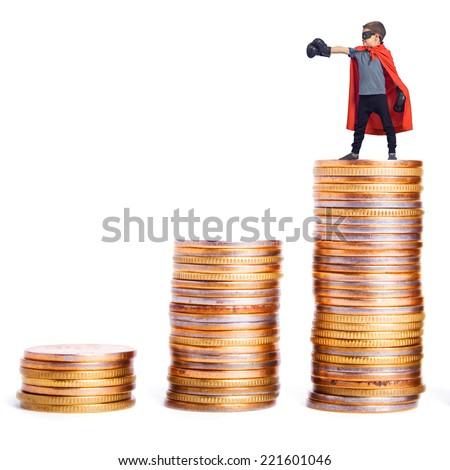 Superhero atop a pile of coins. - stock photo