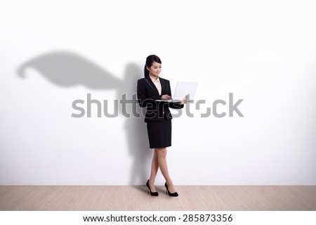 Superhero Business Woman using laptop computer with white wall background, great for your design or text, asian - stock photo