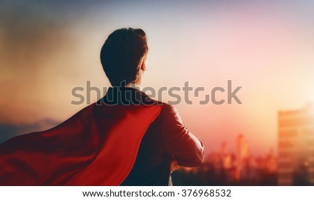 superhero businessman looking at city skyline at sunset. the concept of success, leadership and victory in business. - stock photo