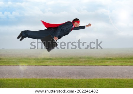 superhero businessman with cape and mask flying  - stock photo