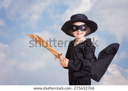 Superhero child with a sword against blue sky background, smiling at the camera, black clothing and a mask - stock photo