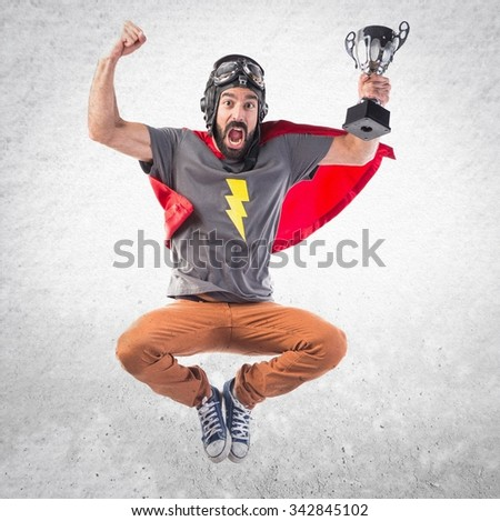 Superhero holding a trophy - stock photo