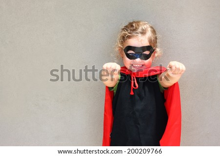 Superhero kid against textured wall background. photographed outdoors under natural light - stock photo