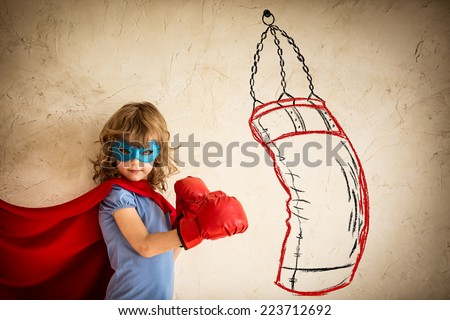 Superhero kid in red boxing gloves. Child punching on the drawn bag. Winner and success concept - stock photo
