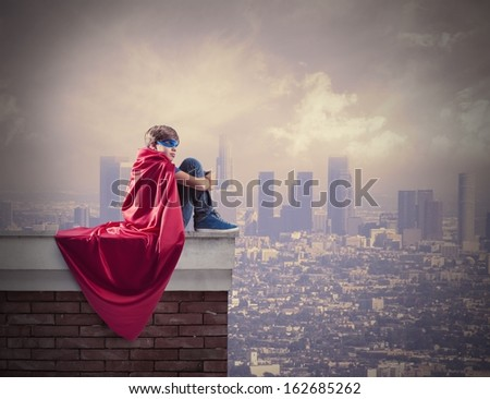 Superhero kid sitting on a wall that controls the city - stock photo
