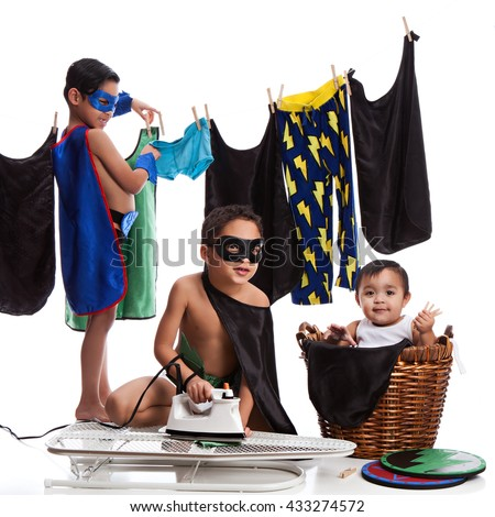 Superhero Laundry Day. Three adorable brothers dressed as superheroes and ironing and hanging their clothes on the line. Isolated on white.