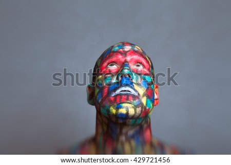 Superhero looking up, colorful face art with tilt shift and motion blur effect. - stock photo