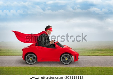 superhero man driving a red toy racing car at speed - stock photo