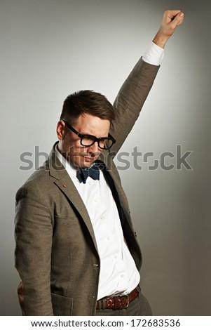 Superhero nerd in eyeglasses and bow tie against grey background - stock photo
