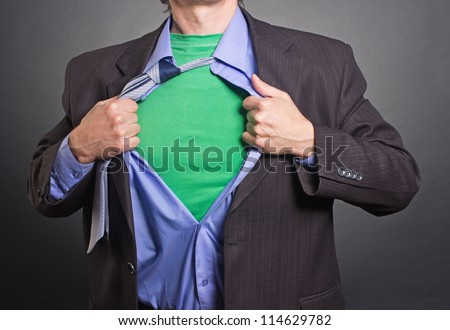 Superhero, young businessman tearing his shirt - stock photo