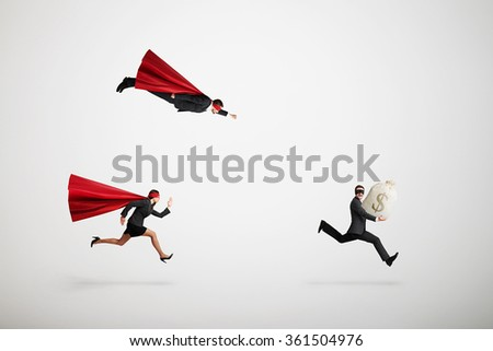 superman and superwoman trying to catch criminals over light grey background - stock photo