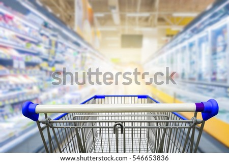 Supermarket aisle with empty blue shopping cart