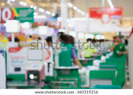 supermarket checkout payment terminal with customers blurred background - stock photo