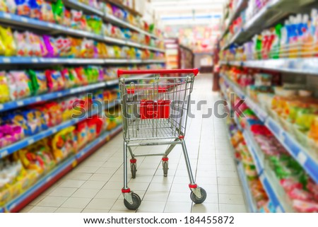 Supermarket interior, empty red shopping cart. - stock photo