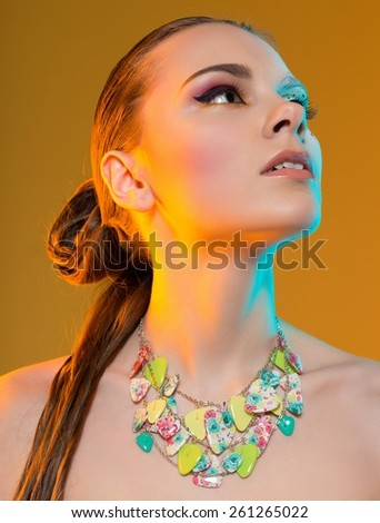 supermodel with creative makeup. in the studio on a yellow background - stock photo