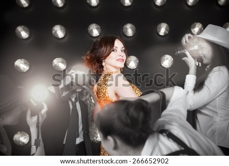 Superstar woman wearing golden shining dress posing to paparazzi - stock photo