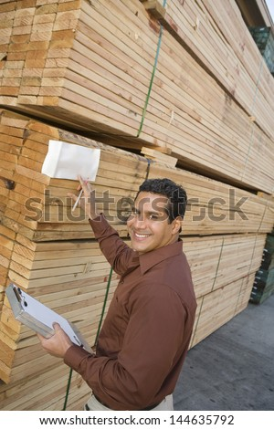 Supervisor checking label on stack of wood in warehouse - stock photo