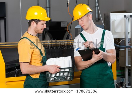 Supervisor checking the quality of finished goods at factory - stock photo