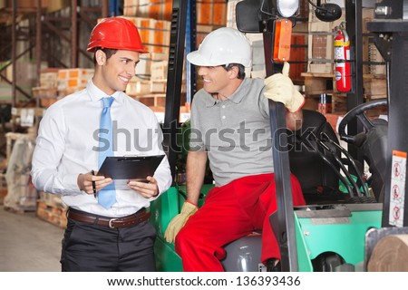 Supervisor communicating with forklift driver at warehouse - stock photo