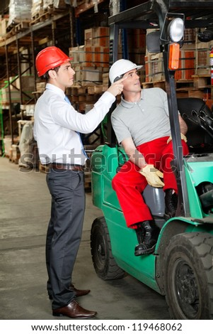 Supervisor instructing forklift driver at warehouse - stock photo