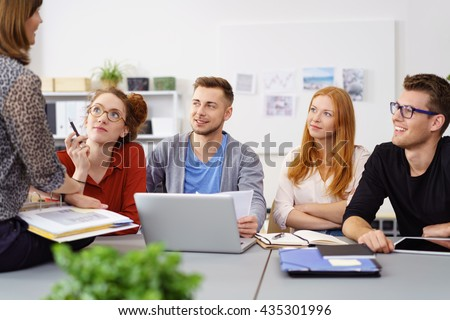 Supervisor or manageress with her business team of dedicated young women and a man sitting on a table in the office having a brainstorming meeting - stock photo