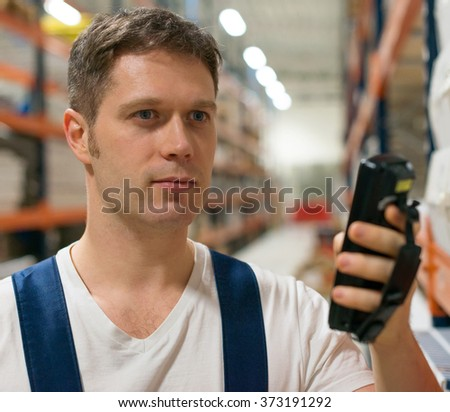 Supervisor scanning package barcode at the warehouse. - stock photo