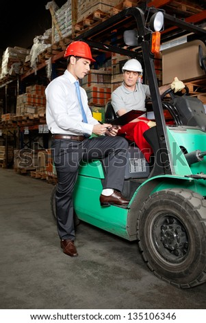 Supervisor showing clipboard to forklift driver at warehouse - stock photo