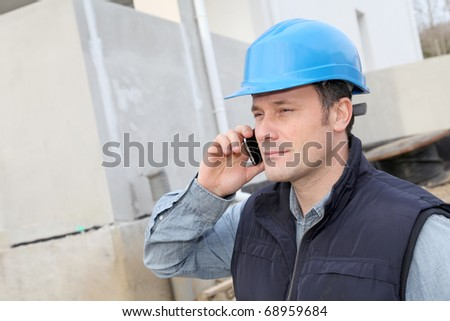 Supervisor talking on the phone on construction site - stock photo