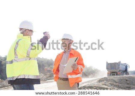 Supervisors discussing at construction site against clear sky - stock photo