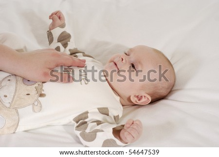 supine baby in the dress of the cow and looking at the mum - stock photo