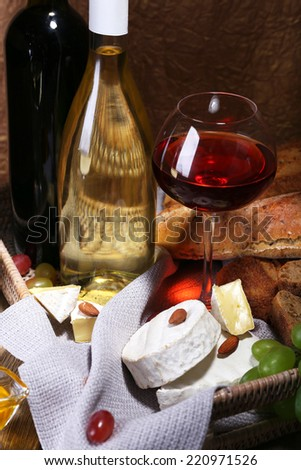Supper consisting of Camembert and brie cheese, honey, wine and grapes on napkin in basket on wooden table on brown background