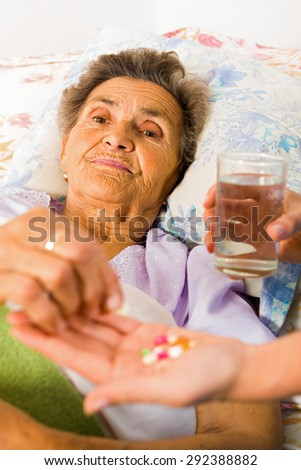 Supplements in nurse's hands for weak senior woman. - stock photo