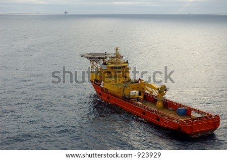 Supply boat with helideck and oil rigs in background - stock photo