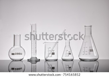 Supply of emptylaboratory glass chemical containers on glass table. Representation in gray tones. Horizontal composition. Front view