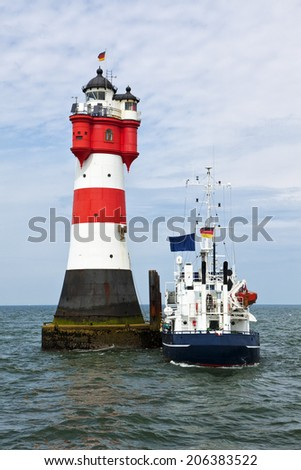 Supply ship moored at lighthouse Roter Sand in the german Wadden Sea - stock photo