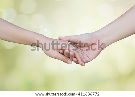 support and assistance human hands on blurred glow green bokeh nature background:helping hand concept.close up soul mate handshake touching together:love affection:better life and take care:nursing - stock photo