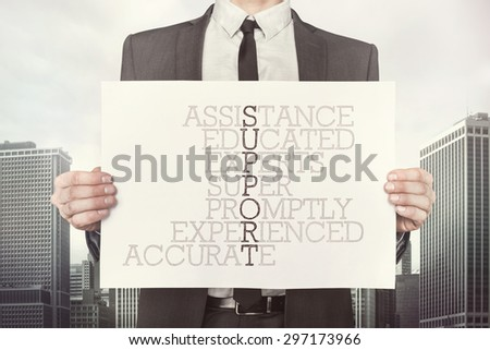 Support crossword concept on paper what businessman is holding on cityscape background - stock photo