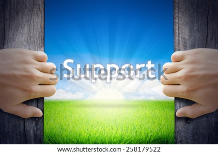 Support. Hand opening an old wooden door and found Support word floating over green field and bright blue Sky Sunrise. - stock photo