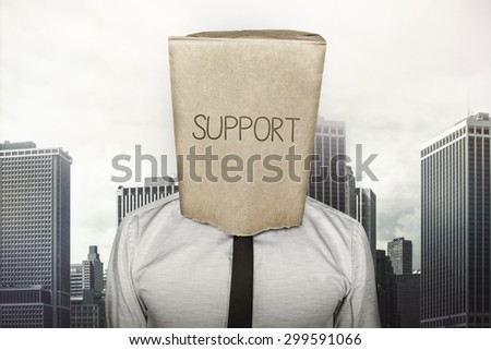 Support text on brown paper bag which businessman has on head on cityscape background - stock photo