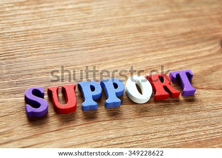 SUPPORT - word made from multicolored child toy  letters on wooden  background - stock photo