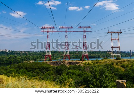 supports of high-voltage power lines against the blue sky - stock photo