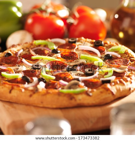 supreme italian pizza with pepperoni and toppings - stock photo