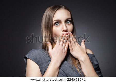 Suprised young woman on dark grey background - stock photo