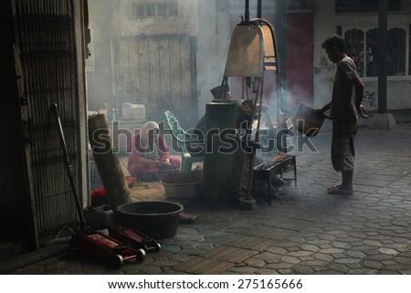 SURAKARTA, INDONESIA - AUGUST 17, 2011: Vendors prepare and sell street food in Surakarta, Central Java, Indonesia.  - stock photo