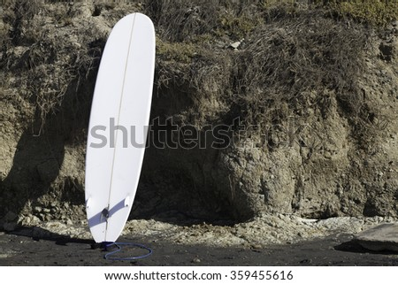 Surboard leaning on cliff at Del Mar, San Diego, California on a sunny winter's day. - stock photo